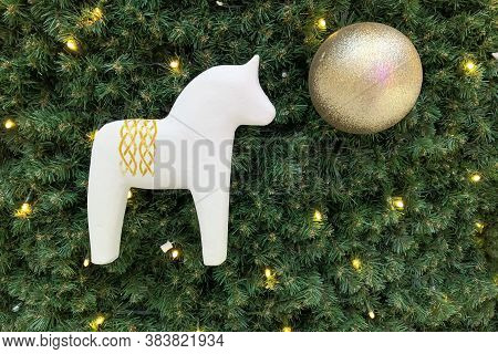 White Wooden Horse And Golden Decorative Ball On The Christmas Tree. Festive Christmas Background Ba