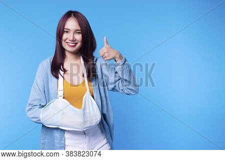 Patient Young Woman Wearing Soft Splint Armband Form Accident Showing Thumb Up While Standing On Blu