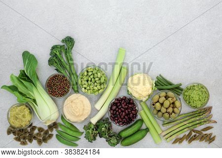 Low glycemic health food for diabetics with vegetables, dips & pasta with all foods below 55 on the GI index. High in antioxidants, vitamins, minerals, protein, smart carbs. Flat lay on mottled grey.