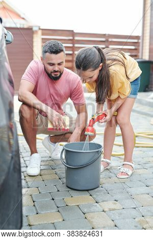 Father sitting on hunkers waiting for his daughter to fill bail with water to wash their car in yard