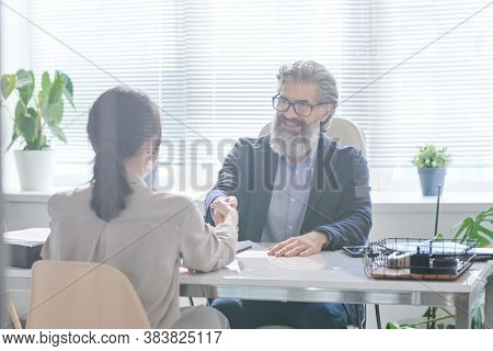Unrecognizable woman succeeding job interview and shaking hands with HR manager sitting in front of her
