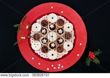 Luxury Christmas mince pies on a red plate with decorative snowflakes, mistletoe & winter berry holly on black background. Flat lay, top view, copy space.