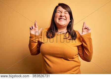 Beautiful brunette plus size woman wearing casual sweater over isolated yellow background gesturing finger crossed smiling with hope and eyes closed. Luck and superstitious concept.