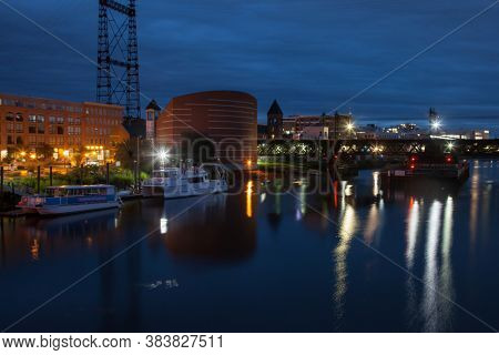 NORWALK,CT, USA-SEPTEMBER 3, 2020: Early morning at Washington Street bridge with Maritime aquarium building and other with water reflections in Norwalk river