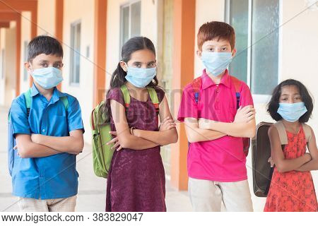Children In Medical Mask With School Backpack Standing With Arms Crossed By Looking To The Camera- C