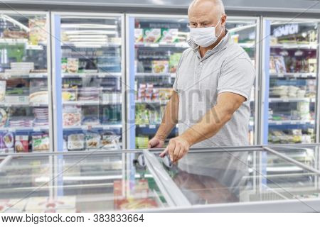 A Masked Man Shopping At A Grocery Store In The Frozen Convenience Store. Coronavirus Pandemic.