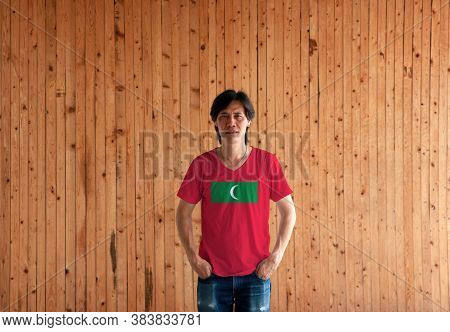 Man Wearing Maldives Flag Color Shirt And Standing With Two Hands In Pant Pockets On The Wooden Wall