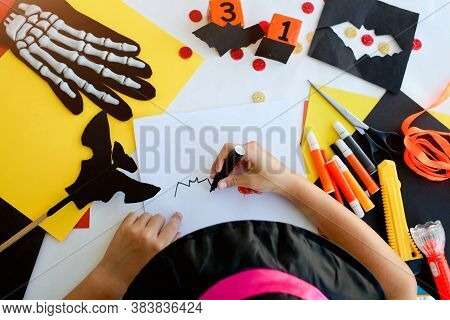 Little Girl In A Witch Costume Draw A Bat, For The Holiday Of Halloween On A Light Table. Halloween