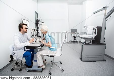 Optometrist And Senior Patient While Vision Diagnostic At A Modern Clinic. Eye Exam And Vision Check