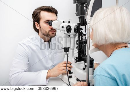 Optometrist Checking Vision To An Old Patient Using A Slit Lamp. Eye Exam Patient With Cataract