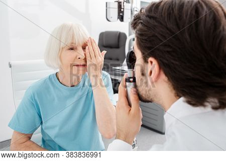 Senior Woman Patient Checking Vision In Opticians Office. Eye Exam And Vision Diagnostic