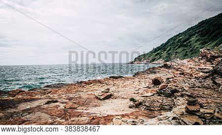 Scenic Layered Rocks   In Blue  Sea Against Sky With Forest Hills Background. Sea Waves Splash On Ro