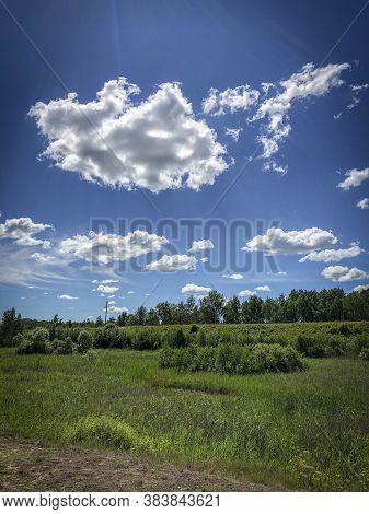 Summer Landscape With Green Grass And Beautiful Clouds