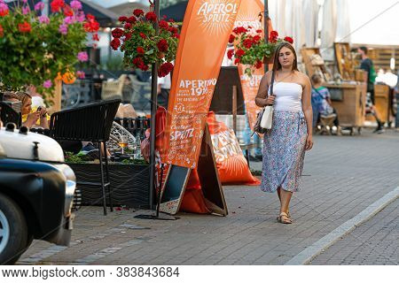 Riga, Latvia - August 21, 2020: A Young Woman Dressed In A Light Top And A Colorful Skirt Walks Down
