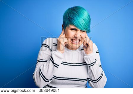 Young beautiful woman with blue fashion hair wearing casual sweater standing at studio covering ears with fingers with annoyed expression for the noise of loud music. Deaf concept.