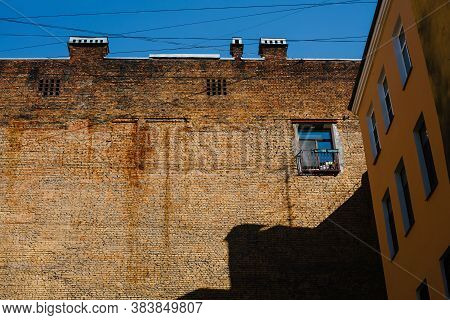 Brick Firewall With One Single Window In Inner Yard, Old Building With Firewall On Sunny Day