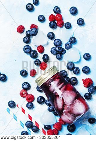 Iced Fruit Tea With Blueberry, Raspberry And Ice In Glass Bottle, Top View