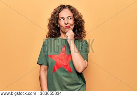 Middle age beautiful woman wearing t-shirt with red star revolutionary symbol of communism thinking concentrated about doubt with finger on chin and looking up wondering