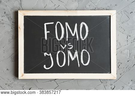 Fomo (means Fear Of Missing Out) And Jomo (means Joy Of Missing Out). Handwritten Text On A Blackboa