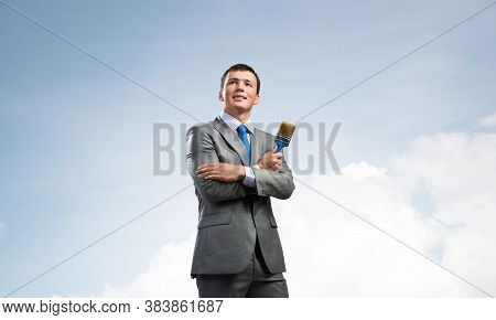 Smiling Creative Businessman Painter Holding Paintbrush In Hand. Joyful Handsome Man In Business Sui