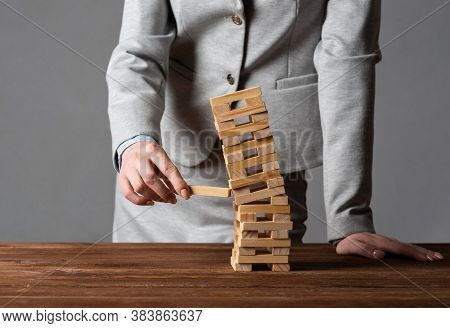 Businesswoman Removing Wooden Block From Falling Tower On Table. Management Of Risks And Economic In