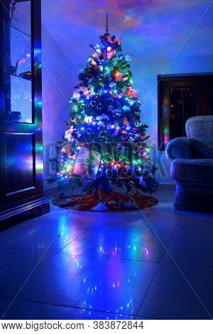 Christmas Tree With Colored Lights. Illuminated Christmas Tree In The Dark Room For The Holidays