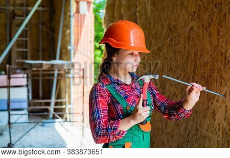 Girl Hammering A Nail. Carpentry And Woodworking Concept. Teen Child Using Hammer Tool. Building And