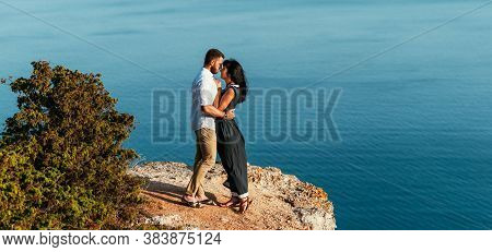 A Couple In Love Embraces On The Beach. A Happy Couple Meets The Dawn By The Sea. Honeymoon Trip. Th