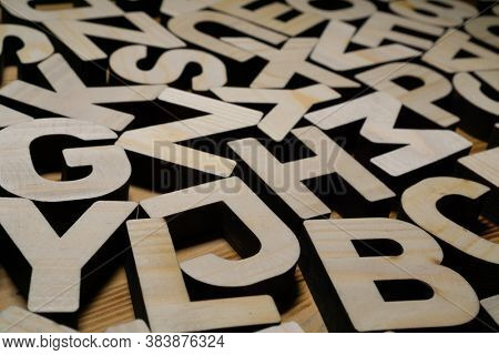 Random wooden block letters lying on wooden surface.