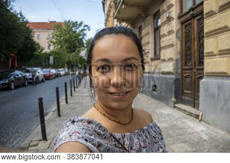 Street Portrait Of A Woman 35-40 Years Old Looking Directly Into The Camera On A Neutral Background