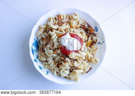 Traditional Soviet Russian Dish Of Pasta, Vermicelli, Sea Paste, With Meat On A White Plate On A Whi