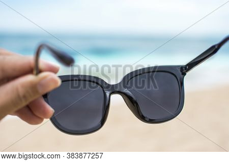 Hand Wearing Sunglasses On The Beach With Blurred Sea Beach Background , Selective Focus