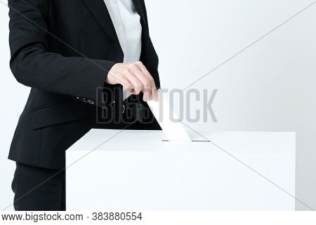 Hands Of A Young Woman Putting Ballots Into An Election Ballot Box