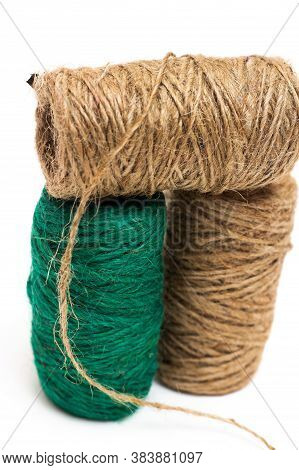 Three Skeins Of Twine. Twine. The Twine Is Brown And Green. On A White Background, String