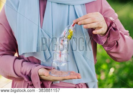 The Girl Is Holding A Jar For Hijama. Hijama, Bloodletting, Treatment Of Sunna. Jars For Bloodlettin