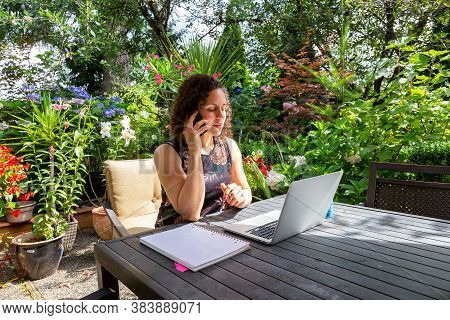Young Caucasian Woman Working On A Laptop From Home In A Garden. Taken In Surrey, Vancouver, British