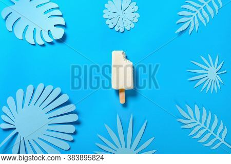 Top View Half Baked Cheese Flavor Popsicle With A Bite On Blue With Hand Cut Flower And Leaves
