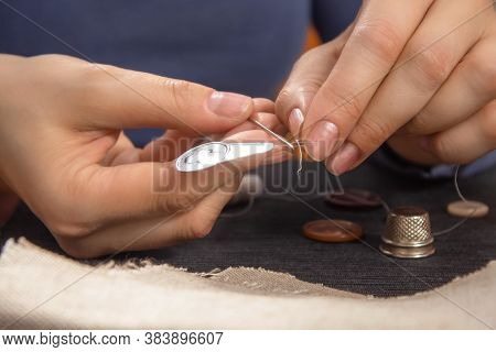 The Threader In The Woman's Hand. Threading The Needle Thread