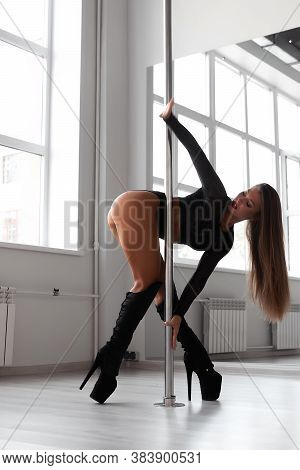 Side View Of Fit Female Dancer In High Heeled Boots And Underwear Hanging On Pole While Rehearsing I