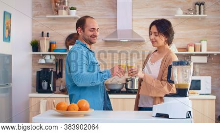 Couple Holding Nutritious Smoothie In Kitchen From Tasty Fruits. Cheerful Family Making Together Org