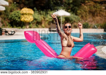 Sexy Woman In Sunglasses Resting And Sunbathing On A Pink Mattress In The Pool. Young Woman In Beige