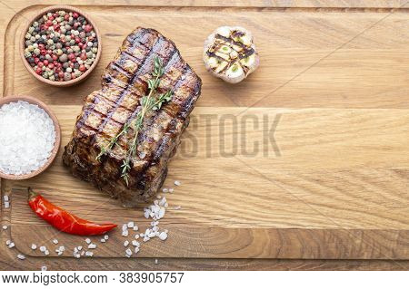 Grilled Steak Grilled On A Wooden Background, With Spices. Grill Strips Visible On Steak