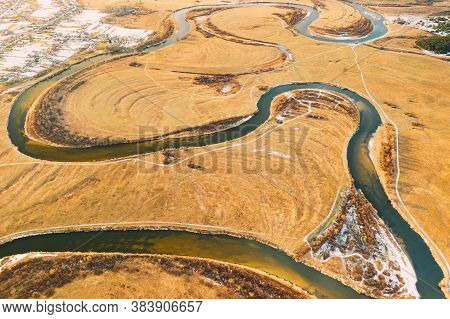 Belarus. Aerial View Of Dry Grass And Partly Frozen Curved River Landscape In Late Autumn Day. High