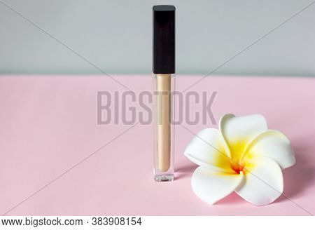 Concealer makeup corrector and flower on pink background, selective focus, copy space for text
