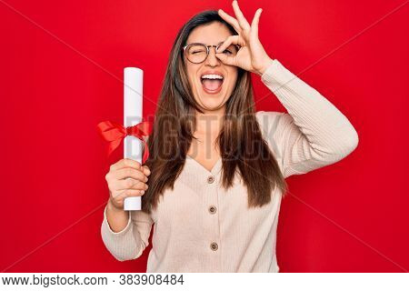 Young hispanic smart woman wearing glasses holding university degree over red background with happy face smiling doing ok sign with hand on eye looking through fingers
