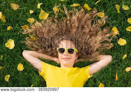 Beautiful Girl Lying On Lawn With Yellow Leaves In Autumn Park