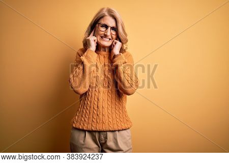Middle age beautiful blonde woman wearing casual sweater and glasses over yellow background covering ears with fingers with annoyed expression for the noise of loud music. Deaf concept.