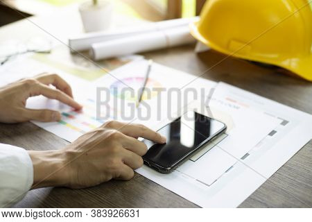 Architect's Desk, Architects Are Comparing Designs In Smartphone, Close Up At Hand.
