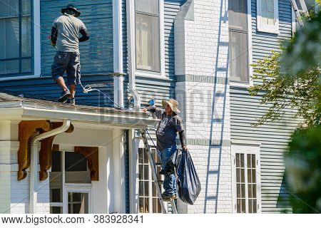 New Orleans, Louisiana/usa - 6/17/2020: Spray Washer And Assistant Working On Roof Of House Prepping