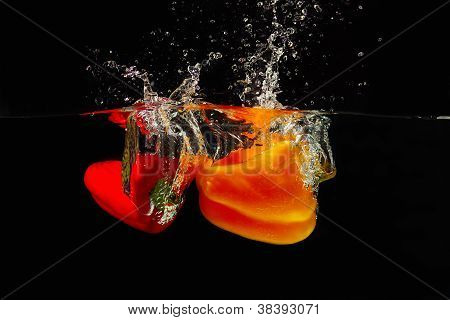 Red and yellow bellpepper falling into the water with a splash on a black background